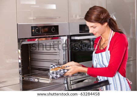 Brunette taking the cake out of the oven - stock photo