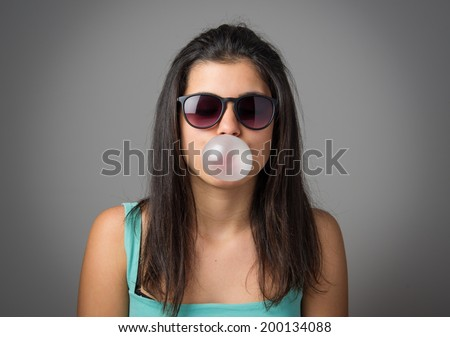 Brunette teenager girl with sunglasses blowing a bubble gum balloon - stock photo