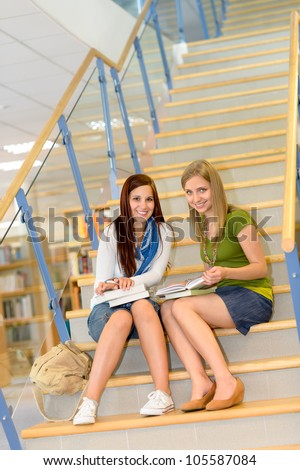 Brunette teenager with classmate studying on high school library stairs - stock photo