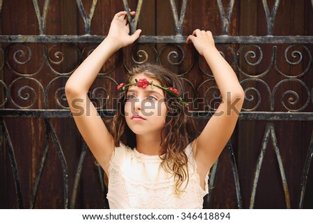 Brunette tourist kid girl in mediterranean old town with flowers in hair - stock photo