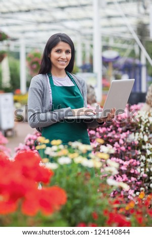 Brunette typing on the laptop in the garden centre while smiling - stock photo