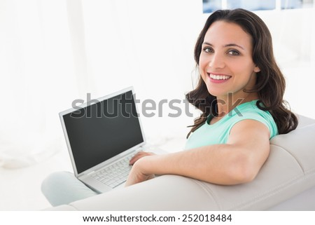 Brunette using her laptop on sofa at home in the living room - stock photo