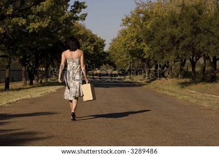 Brunette walking away from camera down tree lane with suitcase and day dress - stock photo