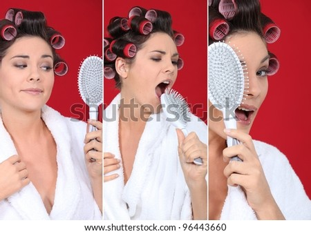 brunette wearing bathrobe with hair curlers holding hairbrush holding  against red background