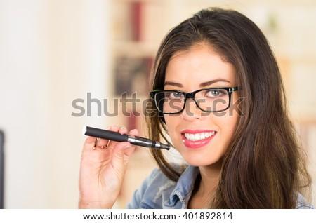 Brunette wearing glasses and bright lipstick holding up e-cigarette, posing for camera - stock photo