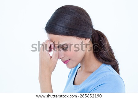 Brunette with a headache and hand on forehead on white background - stock photo