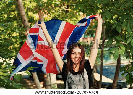 Brunette with britain flag in her hands outdoors in summer - stock photo