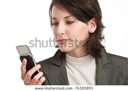 brunette with cellphone, looking at screen, on white background - stock photo