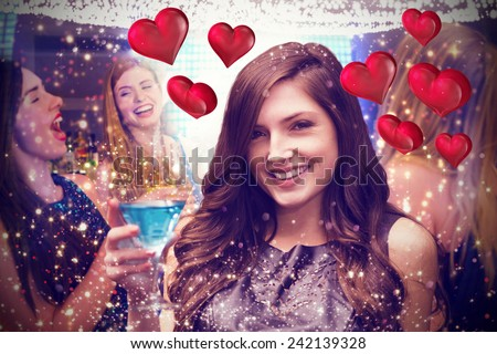 Brunette with cocktail against floating love hearts