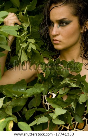 Brunette with dark, dramatic eye shadow posing with green leaves - stock photo