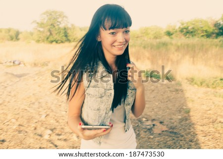 Brunette with digital  tablet outdoors colorized. Blurred motion shot/ Instagram color filter. Mobile communications. Hipster style of life.  - stock photo
