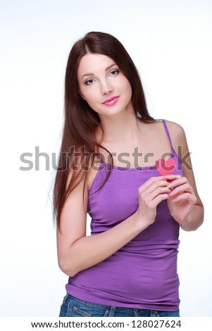 Brunette with long hair holding a paper heart symbol of Valentine's Day