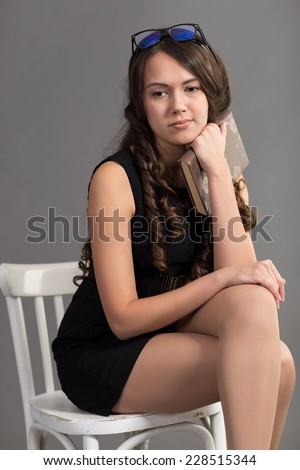 brunette with long hair in black dress sits on white chair with book