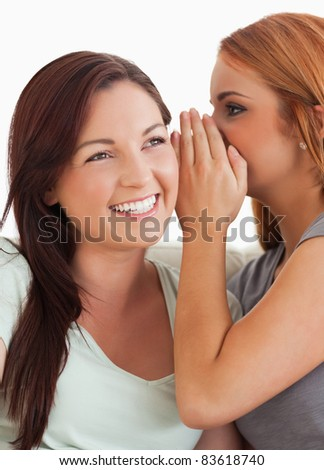 Brunette woman being told a secret in a living room