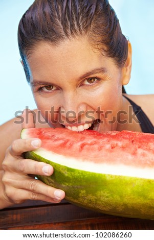 Brunette woman biting with teeth in a watermelon