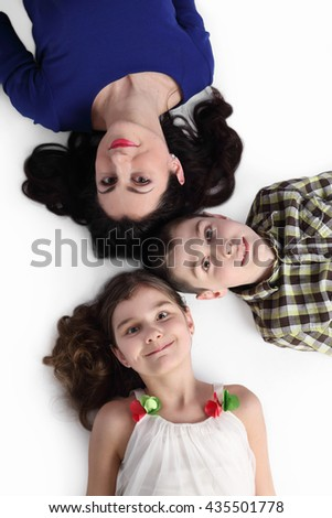 Brunette woman, boy and little girl lie on back looking up on gray background - View from top - stock photo