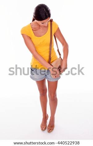 Brunette woman closing her brown handbag and looking down at what she is doing while wearing a yellow t-shirt and short jeans, isolated - stock photo