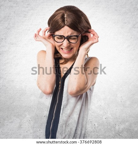 Brunette woman covering her ears over textured background - stock photo