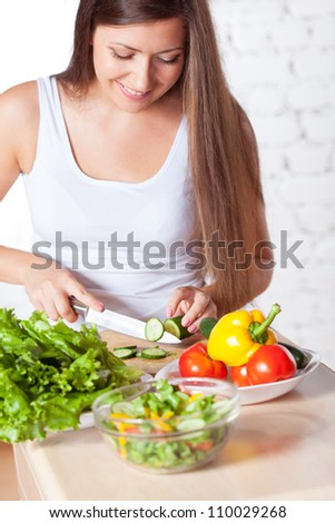 brunette woman cutting  fresh cucumber for salad over white brick wall - stock photo