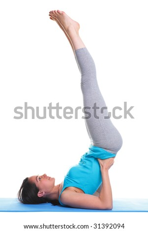 Brunette woman doing a shoulder stand on a yoga mat, isolated on a white background. - stock photo