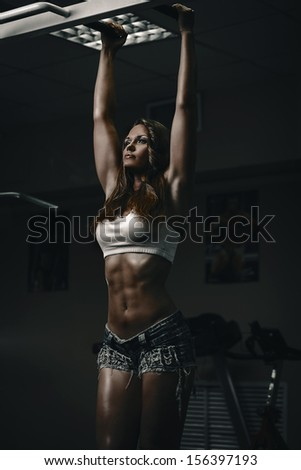 Brunette woman doing pull ups in gym