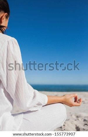Brunette woman doing yoga at beach on a sunny day rear view