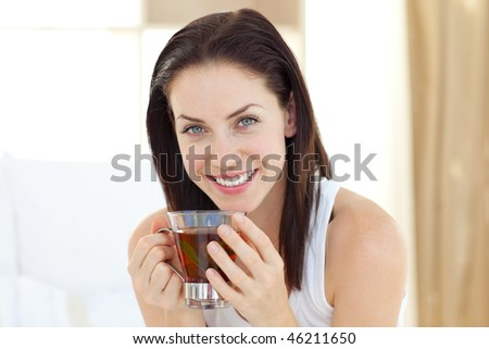 Brunette woman drinking tea sitting on her bed