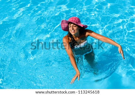 Brunette woman enjoys summer and water in swimming pool. Playful beautiful girl playing with clear water on hot summer day.