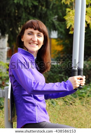 Brunette woman exercising upper body and arms on outdoor gym, concept of healthy and sporty lifestyle