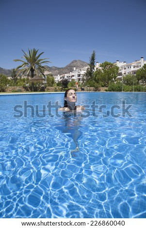 brunette woman face smiling in a big blue pool - stock photo