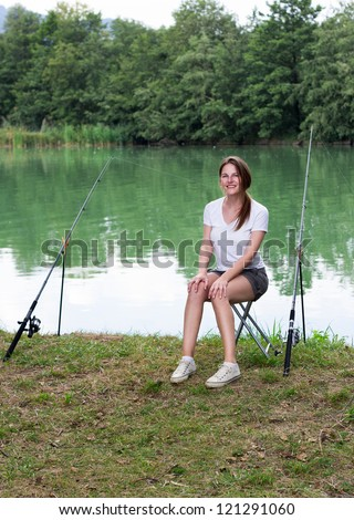 Brunette Woman Fishing at a lake with green water