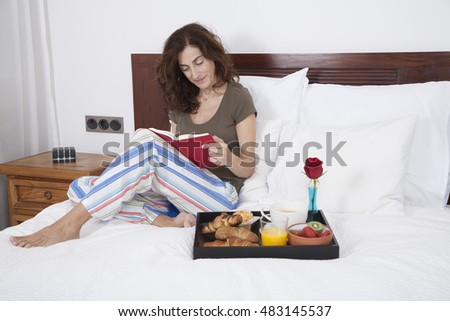 brunette woman green shirt striped pajama pants sitting on white bed reading red book with breakfast tray croissants orange juice strawberry kiwi cupcake red rose flower