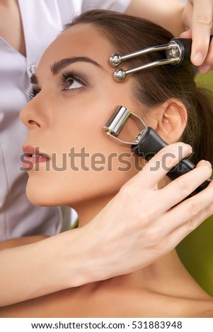 Brunette woman having a stimulating facial treatment from a therapist on the table in professional clinic spa