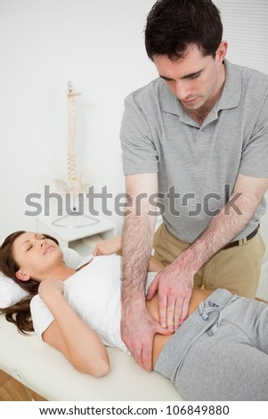 Brunette woman having a stomach ache while lying in a room - stock photo