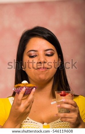 Brunette woman holding delicious brown colored muffin with cream topping, glass of mousse in other hand, big smile and ready to take a bite, pastry concept