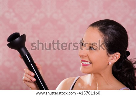 Brunette woman holding plastic nozzle of steam cleaning machine, smiling and pink background - stock photo