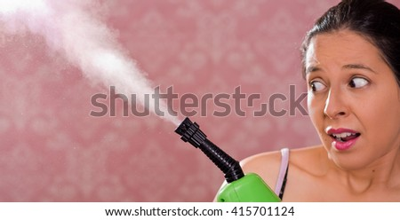Brunette woman holding steam cleaner machine and vapor coming out, scary facial expression, pink background