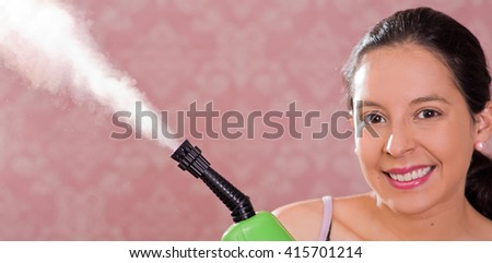 Brunette woman holding steam cleaner machine and vapor coming out, smiling to camera, pink background - stock photo