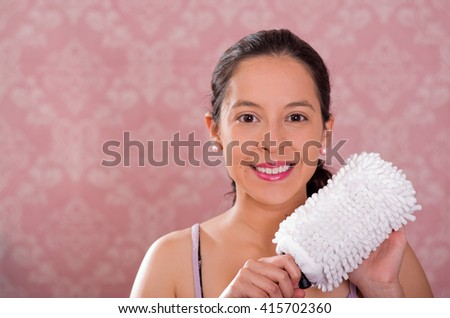 Brunette woman holding white fluffy cleaning brush while smiling to camera, pink background - stock photo
