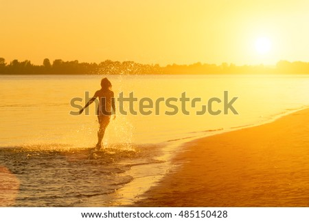 Brunette woman in a dress running along water at sunset or sunrise