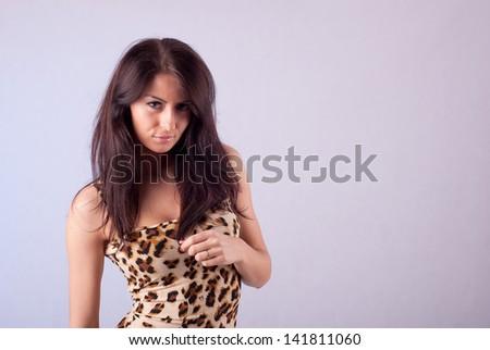 Brunette woman in a leopard print dress - stock photo