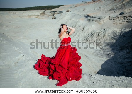 Brunette woman in a long red dress on nature
