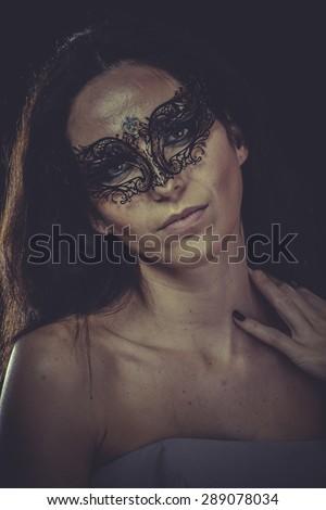 brunette woman in black mask metal frills - stock photo