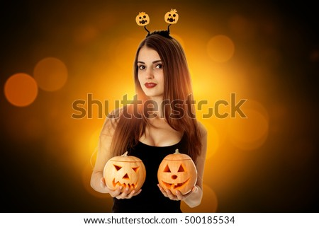 brunette woman in halloween style with two pumpkins in hands looking at camera in studio
