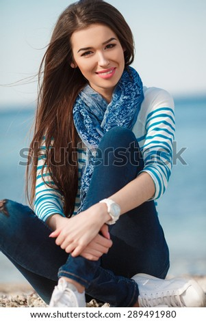Brunette woman in sea style on the sea shore in spring time. Outdoor portrait of young sexy sensual sport woman posing on the sea in sunny weather and have fun in vacation time - stock photo
