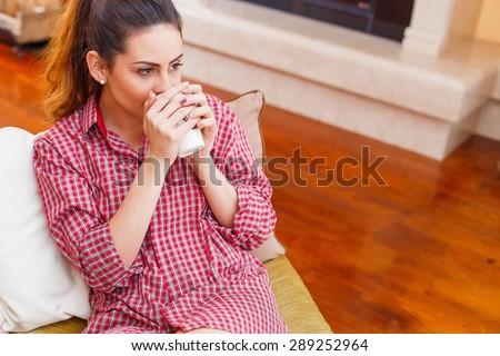 Brunette woman in shirt drinking her morning starter coffee. - stock photo