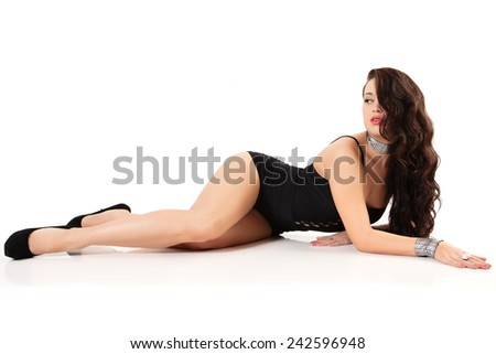 Brunette woman in swimsuit studio shot. White closeup background. Model posing on floor. - stock photo