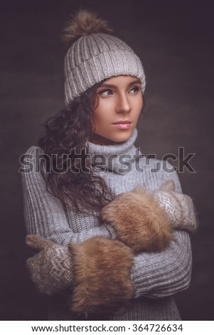 Brunette woman in warm pullover and winter hat.