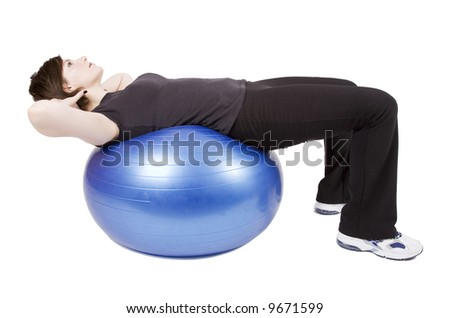 Brunette woman in workout clothes doing abdominal exercises on an exercise ball. Isolated on white.