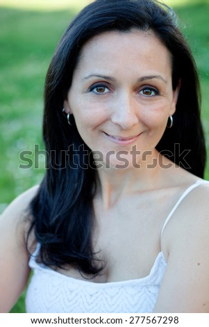 Brunette woman looking at camera on a flowered meadow